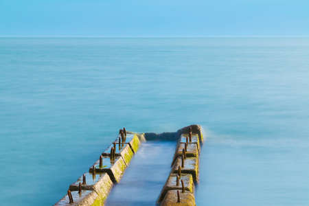 Long exposure view of the concrete mole in the sea and horizon far away in sunny day Stock Photo