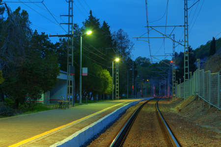 The railway station with the illuminated platform and the railroad going into the distance at twilight, Sochi, Russia