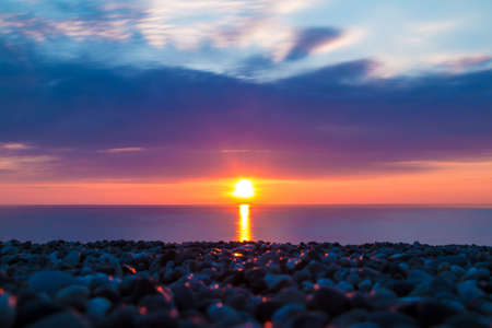Long exposure view of the pebble beach on the background of the setting sun over the sea