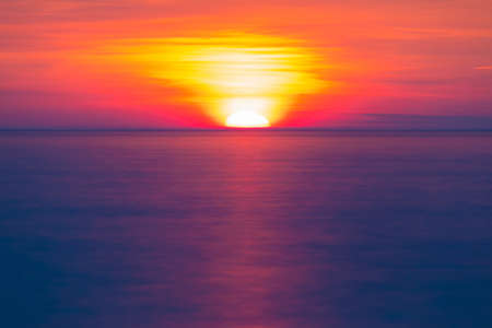 Long exposure view of the half of setting sun over the sea horizon Stock Photo