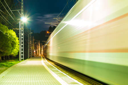traction: The illuminated platform of railway station and train in motion blur at dusk, Sochi, Russia Stock Photo