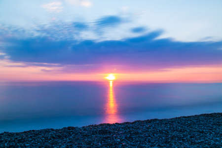 Long exposure view of the pebble beach on the background of sunset over the sea