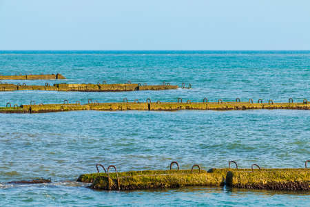 Row of the concrete moles in the sea and horizon far away in sunny day
