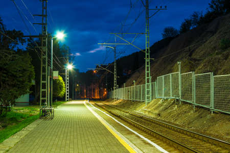 The illuminated platform of railway station and the railroad going into the distance at twilight, Sochi, Russia