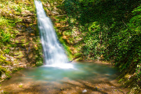 Long exposure photo of the waterfall and little lake in the park Berendeyevo Tsarstvo in sunny summer day, Sochi, Russia