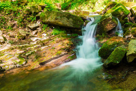Waterfall and boulders in the park Berendeyevo Tsarstvo in sunny summer day, Sochi, Russia Stock Photo