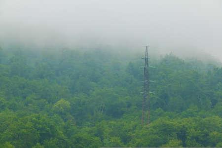 Een transmissietoren die zich in het midden van bos op berghelling met dichte mist bevindt Stockfoto - 88892082