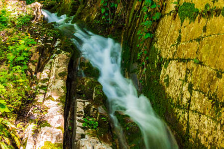Little waterfall and the steep wall in the park Berendeyevo Tsarstvo in sunny summer day, Sochi, Russia Stock Photo