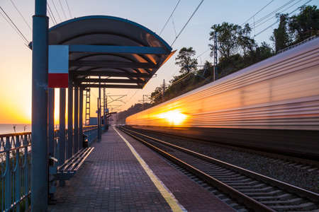 The platform of railway station and train in motion blur at sunset, Sochi, Russia