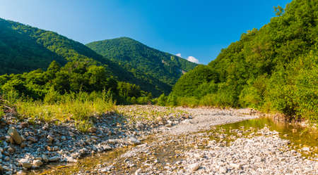 Panoramic view of Makopse river flowing in ravine on the background of Tamyurdepe mountain in the light of the setting sun, Sochi, Russia Stock Photo