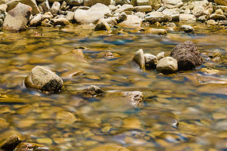 Long exposure photo of the river flowing in rocky ravine in sunny day Stock Photo