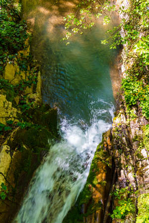 Top view of the waterfall in the park Berendeyevo Tsarstvo in sunny summer day, Sochi, Russia