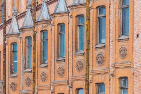 Several windows in row on facade of urban apartment building angle view, St. Petersburg, Russia