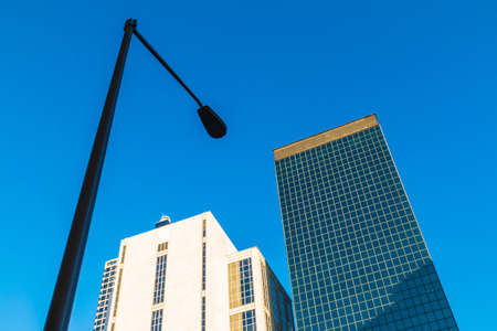Bottom view of streetlight and office skyscrapers on the background of clear sky, Atlanta, USA