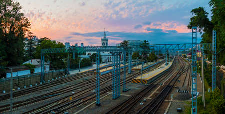 Aerial panoramic view of the Sochi railway station with many railroads and traction line towers at sunset, Russia