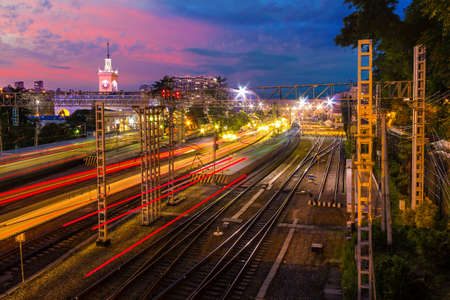 Long exposure aerial view of the Sochi railway station with motion blurred trains at twilight, Russia