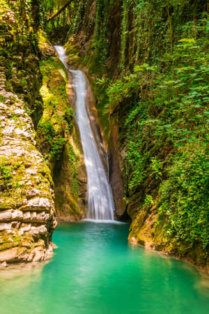 Waterfall and lake in the ravine Chudo-Krasotka in sunny summer day, Sochi, Russia