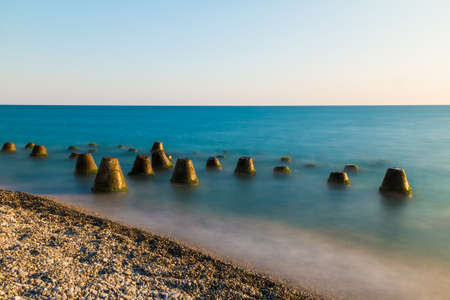 Long exposure photo of the concrete conical boulders lying in the sea near the beach