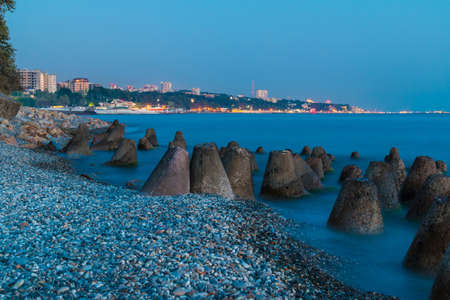 Long exposure photo of the concrete conical boulders lying in the sea on the background of coastline of Sochi at twilight, Russia