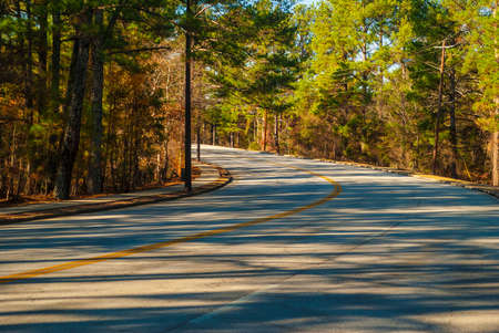 The turn of the Robert E Lee Boulevard with long shadows of trees in the Stone Mountain Park in sunny autumn day, Georgia, USA