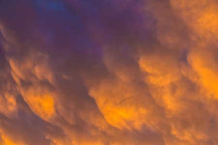 Beautiful cloudscape with colorful contrasting mammatus clouds at sunset