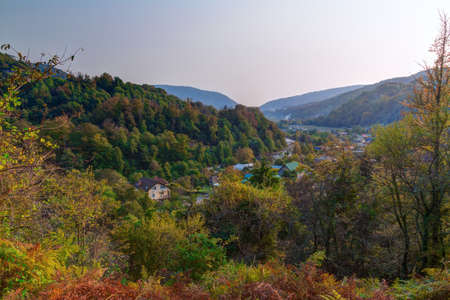 Landscape of Plastunka village in the valley and mountains with varicolored trees in sunny autumn day, Sochi, Russia Stock Photo