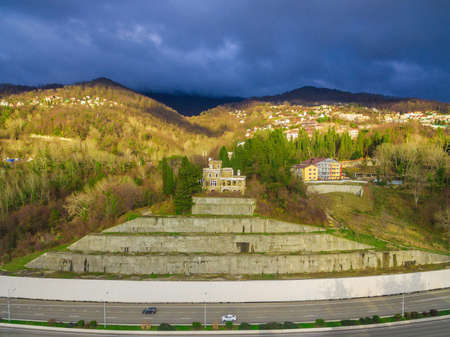 Drone view of the abandoned old mansion called Dacha Kvitko near Kurortnyy Prospekt and mountains in the rays of the setting sun, Sochi, Russia