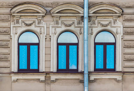 Three windows in a row on the facade of the urban historic building front view, Saint Petersburg, Russia Stock Photo