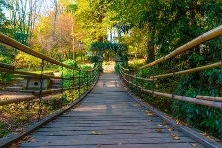 Low-angle view of the suspension bridge with stone archs in Arboretum in sunny autumn day, Sochi, Russia Archivio Fotografico