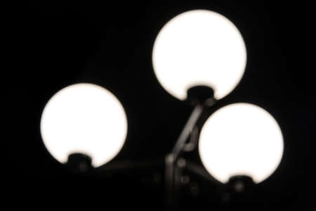 Low-key photograph of a blurred luminous streetlight with three lamps on a black background closeup Stock Photo