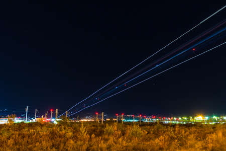 Light trails of landing plane on the background of night sky with stars, Adler, Sochi, Russia