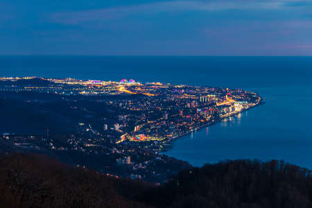 Beautiful aerial view of the illuminated city of Sochi and the sea from the peak of Mount Akhun in the dusk, Russia Stock Photo
