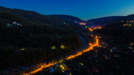 Drone view of mountains and illuminated road in the Plastunka village in the valley of the Sochi river at dusk, Sochi, Russia
