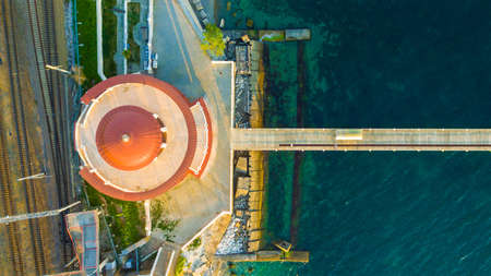 Top-down drone view of the Matsesta marine station near the railroad and the pier in sunny summer day, Sochi, Russia
