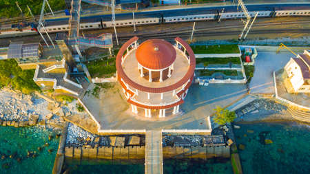 Drone view of the Matsesta marine station near the railroad with a train in sunny summer day, Sochi, Russia