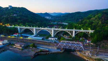 Drone view of the illuminated Matsesta viaduct and railway bridge on the background of mountainsides with dense forest at twilight, Sochi, Russia