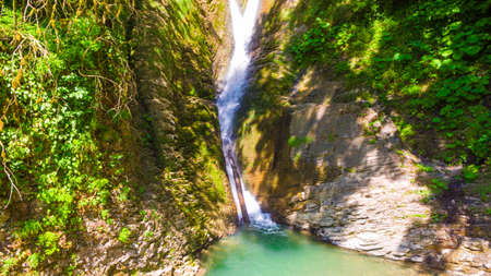 Drone view of Orekhovsky waterfall and vegetation on the steep rock in sunny summer day, Sochi, Russia