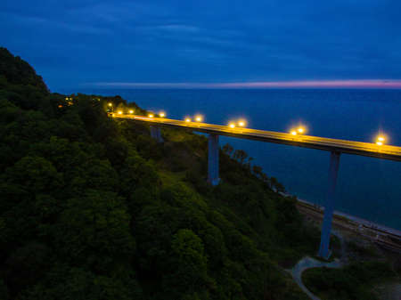 Drone view of the illuminated Zubova Schel viaduct and mountainside with forest on the background of the sea at dusk, Sochi, Russia