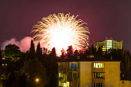 A festive fireworks over the apartment buildings and trees at dusk, Sochi, Russia Stock Photo