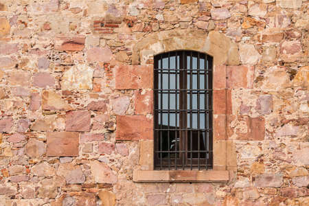 A window on the stone facade of the Montjuic Castle front view, Barcelona, Spain