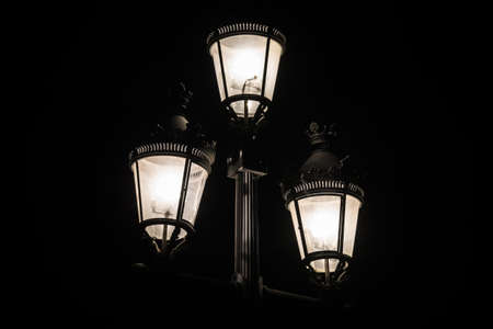 Low-key photograph of a luminous streetlight with three lamps on a black background closeup
