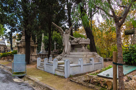 The grave with sculpture of angel closeup and other graves on Montjuic Cemetery in autumn overcast day, Barcelona, Catalonia, Spain