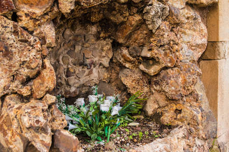 White roses in the stone wall with a tap for watering on the Montjuic Cemetery, Barcelona, Catalonia, Spain Banco de Imagens