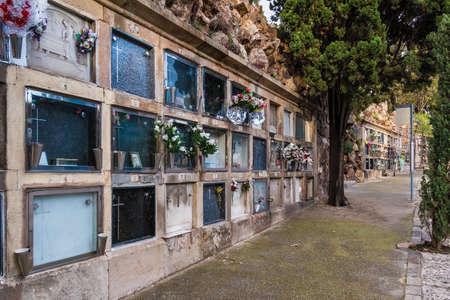 Vista en perspectiva del sendero con tumbas en el cementerio de Montjuic en días nublados, Barcelona, Cataluña, España