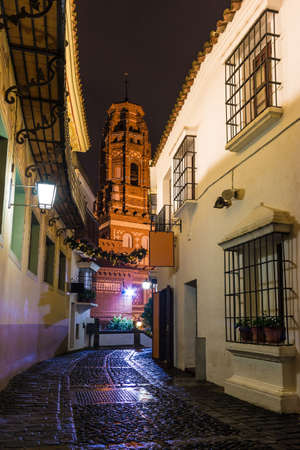 Barcelona, Catalonia, Spain - November 17, 2018: Beautiful night view of an illuminated street, buildings and bell tower in the open-air Poble Espanyol architectural museum