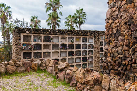 The stone walls with graves on the Montjuic Cemetery in overcast day, Barcelona, Catalonia, Spain