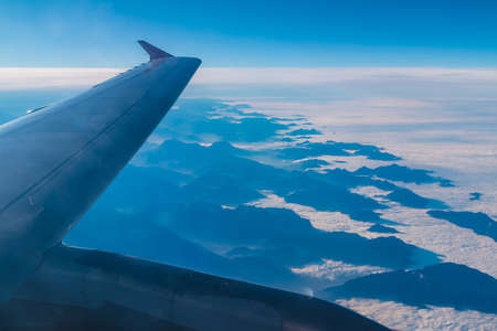 The wing of the airplane above a mountains hiding in the clouds closeup, view from the porthole