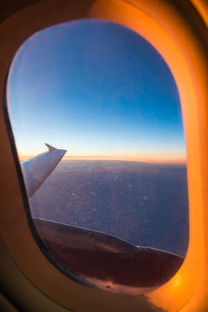 The wing of the airplane above a clouds, view from the porthole beautifully illuminated by the setting sun