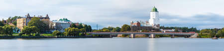 Long-exposure panoramic view of the Vyborg Castle, the Petrovsky Bridge and apartment buildings in overcast day, Vyborg, Leningrad Oblast, Russia Banco de Imagens