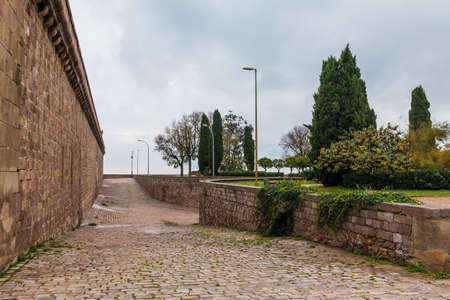 Barcelona, Catalonia, Spain - November 16, 2018: Perspective view of the pavement and fortress of the Montjuic Castle in overcast day